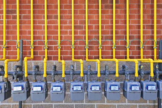 Row of natural gas meters with yellow pipes on building brick wall