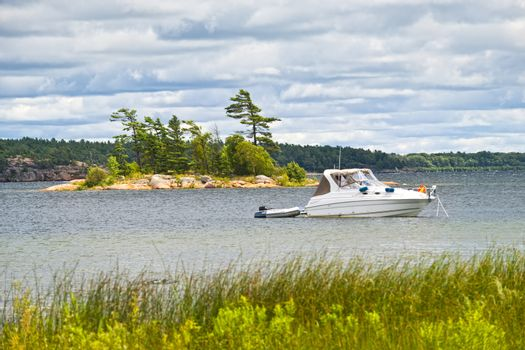 Motorboat anchored with dinghy on lake in Georgian Bay, Ontario, Canada