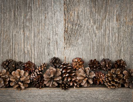 Rustic natural wooden background with pine cones