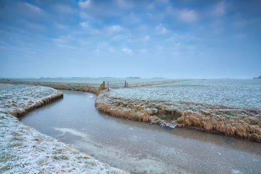 frozen canal on Dutch farmland