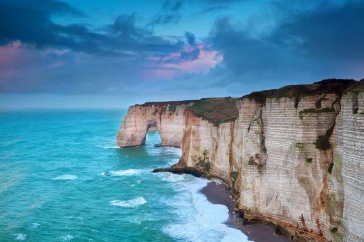 rocky cliff in azure ocean waves