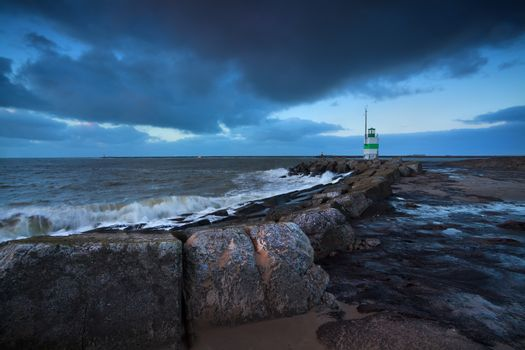 green lighthouse in dusk on North sea