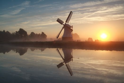 sunrise behind Dutch windmill