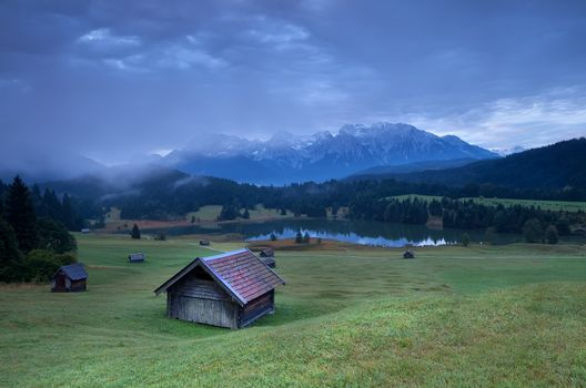wooden hut on alpine meadow by lake
