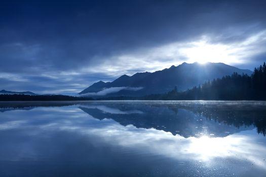 sunshine over mountains and alpine lake