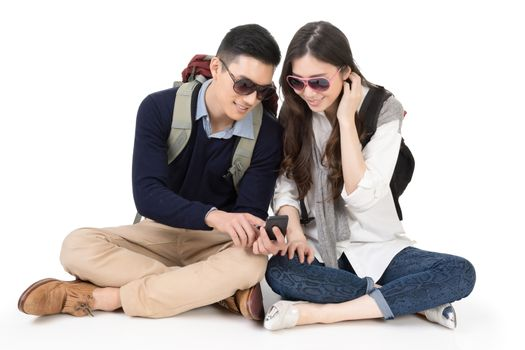 Happy traveling Asian couple sitting on ground and using cellpho
