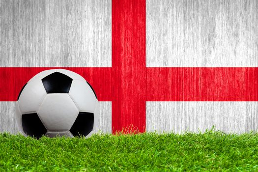 Soccer ball on grass with England flag background