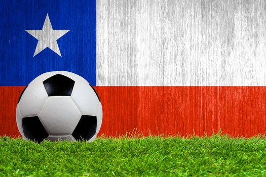 Soccer ball on grass with Chile flag background