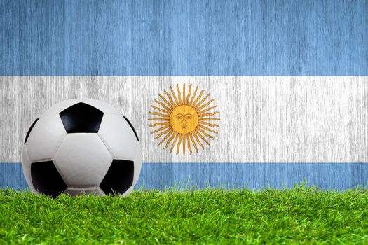 Soccer ball on grass with Argentina flag background