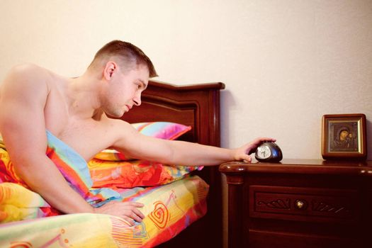 man in bed switching of the alarm clock