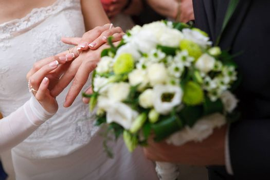 bride puts on a wedding ring to a groom