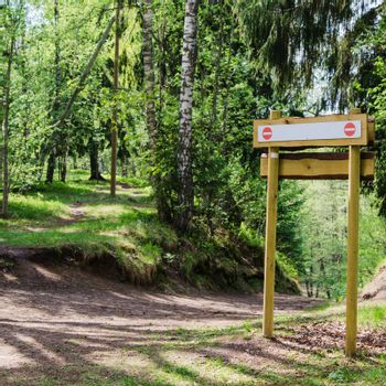 Wooden sign board on the natural trail. In the   forest park