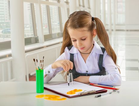 beautiful litle schoolgirl siiting at table and drawing with com