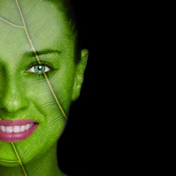 Nature concept - woman face covered with leaf texture