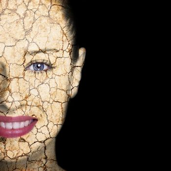 Beauty concept - woman face covered with cracked surface - symbol of dry skin