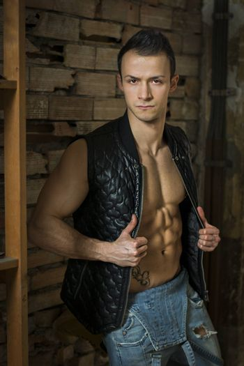 Muscular shirtless young man with jeans and sleeveless jacket