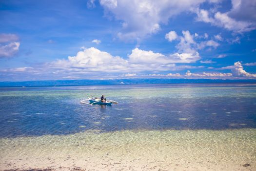 Poor Fisherman in boat at clear blue sea Philippines