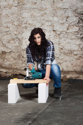Young long-haired woman with a circular saw