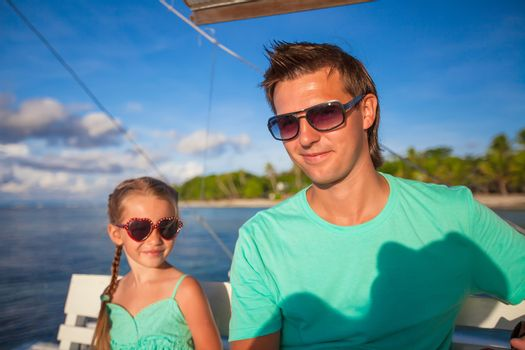 Little adorable girl with young dad relax while sailing on the boat