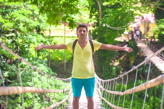 Young guy on suspension bridge over the River Loboc, Philippines