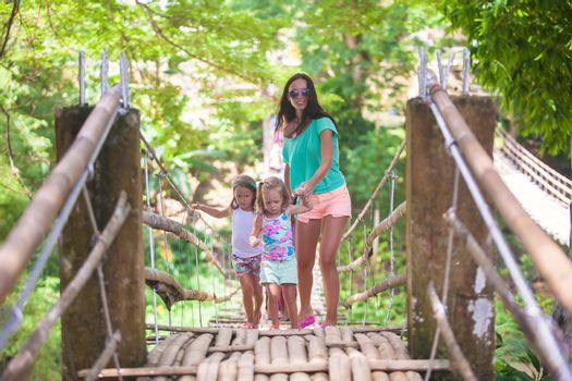 Young mother with her little girls on suspension bridge over the River Loboc, Philippines