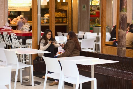 LIMA, PERU - JULY 23, 2013: Unidentified young women sitting with cell phones on bench in the food court of the shopping mall Larcomar on July 23, 2013 in Miraflores, Lima, Peru. Larcomar is a very popular shopping mall in Lima built into the steep coast of Miraflores overlooking the Pacific Ocean.