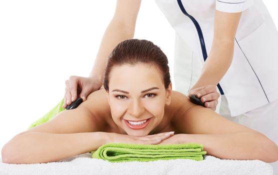 Beautiful woman on spa salon having stone massage.