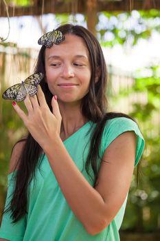 Young girl watching butterflies in a natural garden
