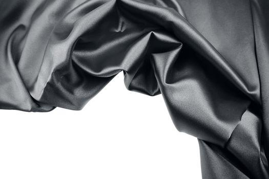 Closeup of rippled black silk fabric on plain background