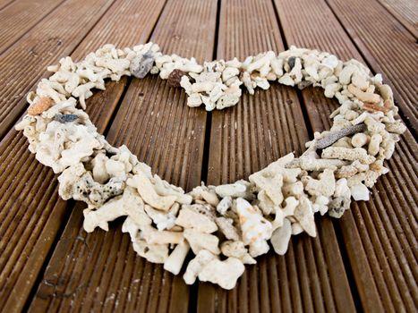Heart shaped seashells on a wood planks