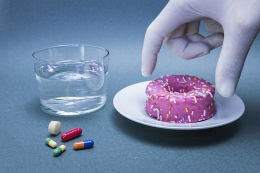 Various medicines to combat diabetes along with a sweet cake, concept of disease of hyperglycemia or diabetes