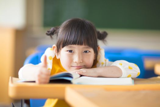 smiling kid lie prone on a desk and thumb up