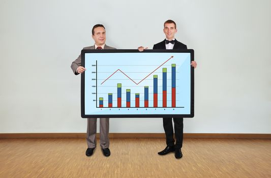 two businessman in room holding plasma panel with graph