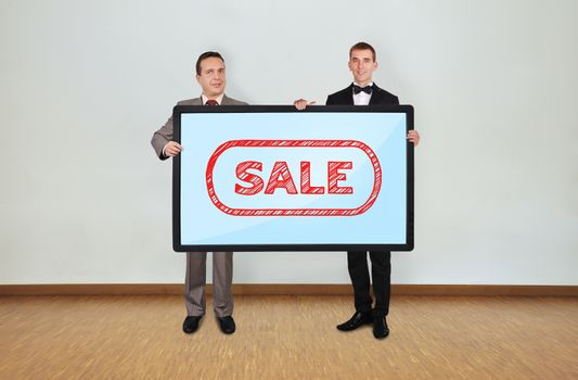 two businessman in room holding plasma panel with sale