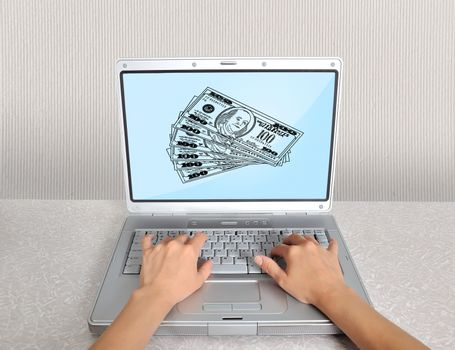 hands and laptop with money on the table
