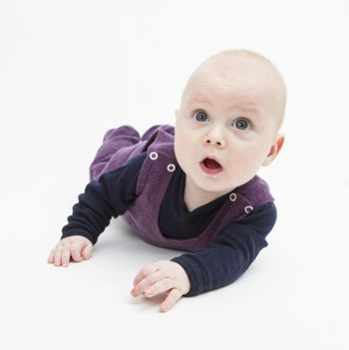 astonished baby lying on floor. studio shot on grey background