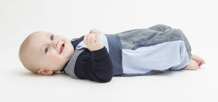baby boy laying on floor. neutral grey background. studio shot