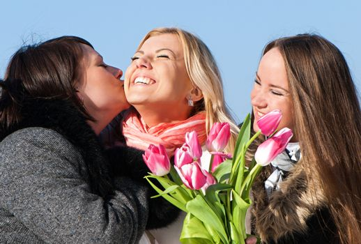 Happy three beautiful young women with pink tulips