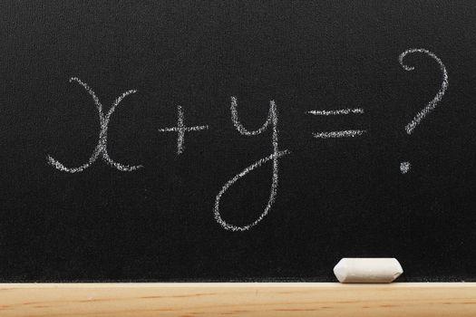 Mathematical equation written on a blackboard by a chalk