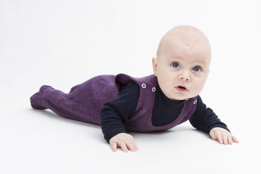 baby on floor looking to camera. studio shot in grey background