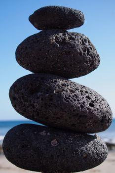 Isolated stacked zen stones near seashore