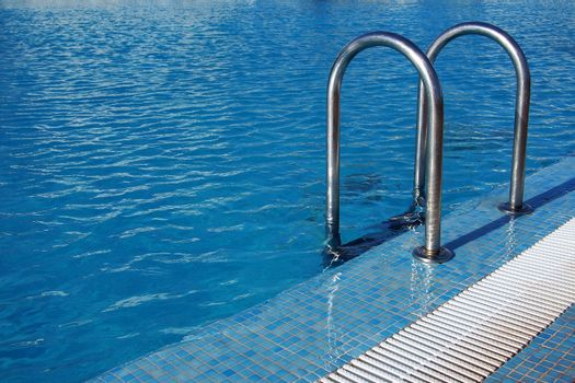 Swimming pool with steel ladder