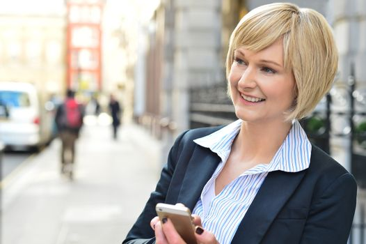 Corporate woman operating her cellphone