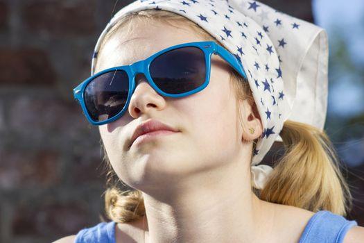 portrait of a cute little girl wearing sunglasses