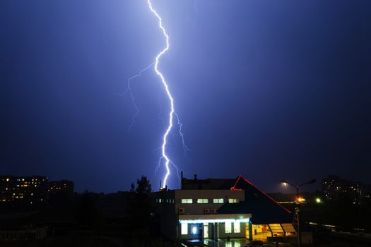 Severe lightning storm over a city buildings