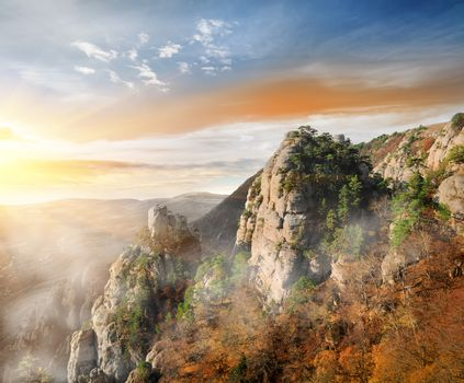 Sunrise and fog in the canyon of mountains