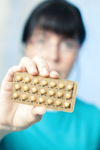 Young woman holds birth control pills