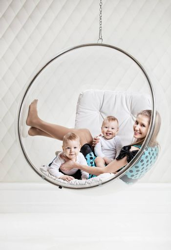 Young Caucasian woman with two babies having fun while sitting in swinging hanging chair