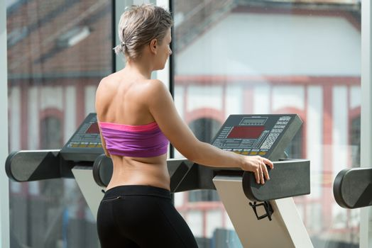 Girl Exercising On Step Machine In Fitness Club