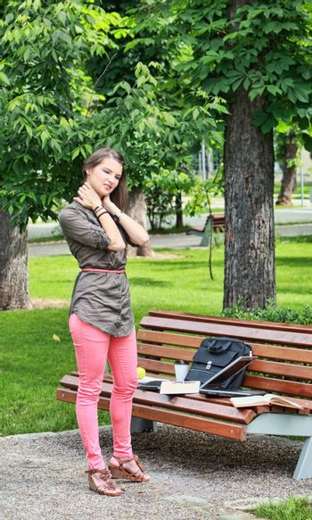 Young woman massaging her nape near a bench in a park during a short break of her work on laptop.